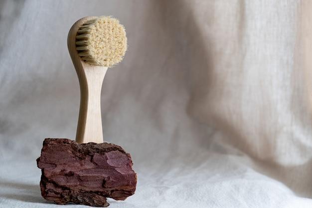 나무 껍질과 말린 꽃과 린넨 배경에 천연 강모가있는 얼굴 마사지 브러시. 친환경 화장품 개념.