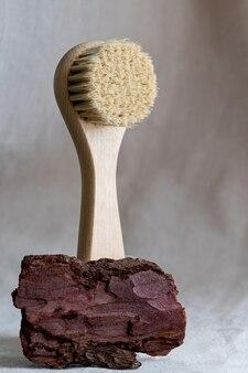 나무 껍질과 말린 꽃이있는 린넨 표면에 천연 강모가있는 얼굴 마사지 브러시. 친환경 화장품 개념.