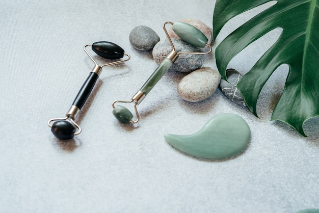 얼굴 마사지 도구 : 자갈 돌과 열대 몬스 테라 잎이 달린 옥 구 아샤 마사지 롤러 및 스크레이퍼