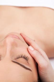 Массаж лица. вид сверху привлекательной молодой женщины, лежащей и с закрытыми глазами, пока массажист массирует ее лицо
