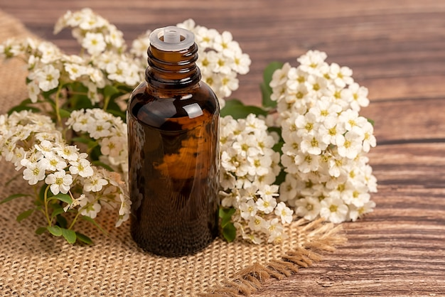 Facial oil, serum or cannabis oil. natural cosmetic. flowers are white on sackcloth. on a wooden background.