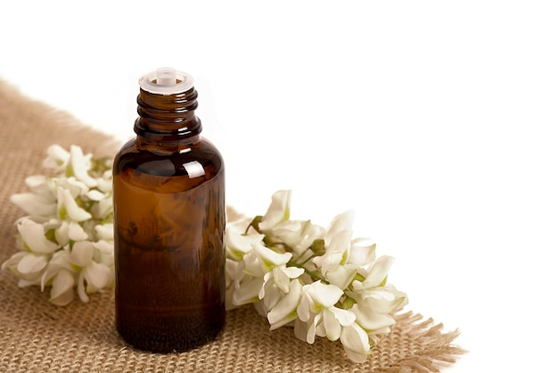 Facial oil, serum or cannabis oil. natural cosmetic. white flowers on a white background.