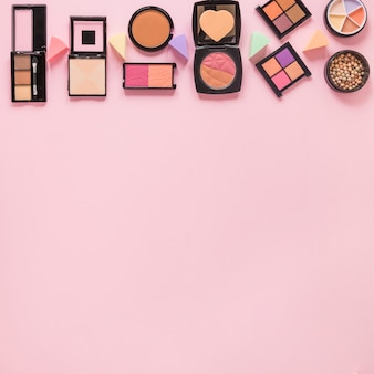 Facial powders with eye shadows on pink table