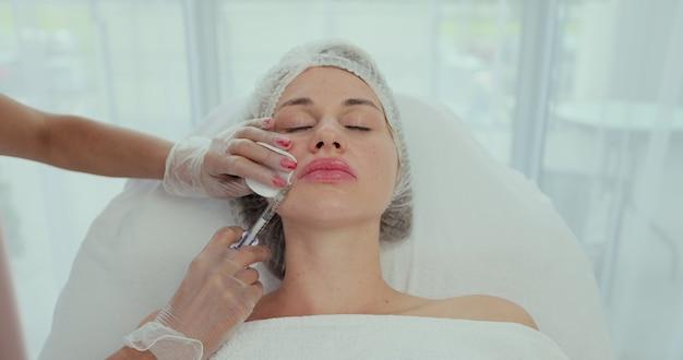 얼굴 회춘 절차 - 여성 의사는 젊은 여성 고객에게 히알루론산 주사를 비순 주름에 주사합니다.