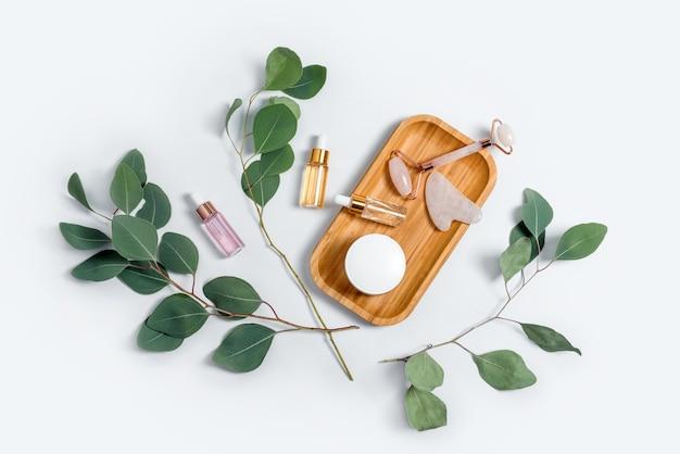 밝은 배경에 천연 유칼립투스 잎이있는 페이셜 롤러, 에센셜 오일 또는 화장품 세럼 및 화장품 크림