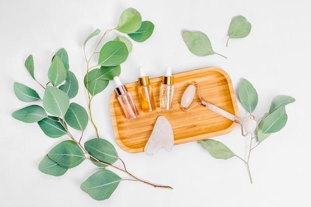 밝은 배경에 천연 유칼립투스 잎이있는 페이셜 롤러, 에센셜 오일 또는 미용 세럼.