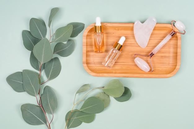 민트 그린 배경에 천연 유칼립투스 잎이있는 페이셜 롤러, 에센셜 오일 또는 미용 세럼