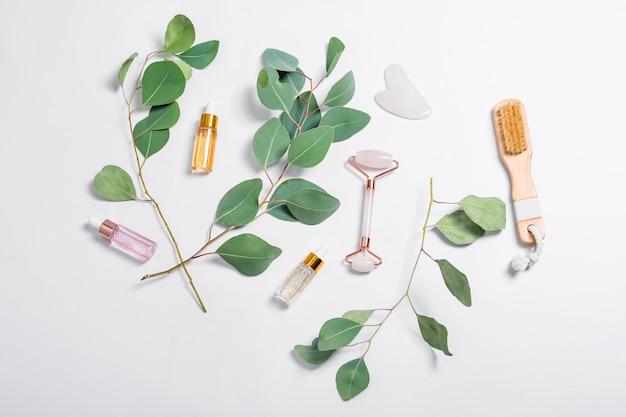 밝은 배경에 천연 유칼립투스 잎이있는 페이셜 롤러, 마사지 브러시, 에센셜 오일 또는 미용 세럼.