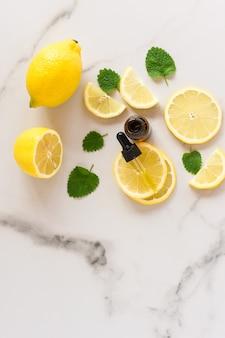 Сыворотка для лица в стеклянном флаконе с пипеткой, листьями мелиссы и дольками лимона на мраморном столе. натуральные органические средства ухода за собой. вид сверху.