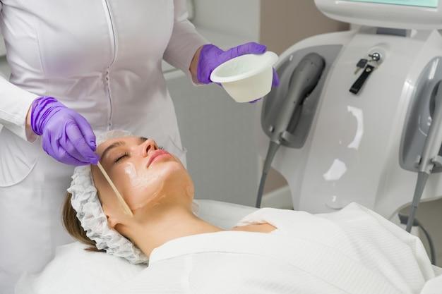 Уход за кожей лица. маску накладывают на лицо женщины в косметологической клинике. закрыть вверх