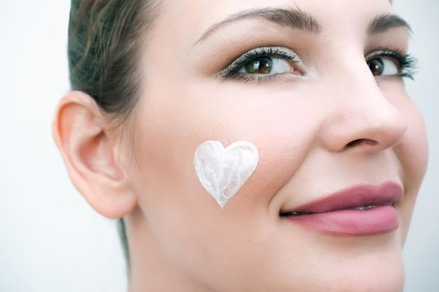 Концепция ухода за кожей лица. у молодой женщины кремовое сердечко на лице.