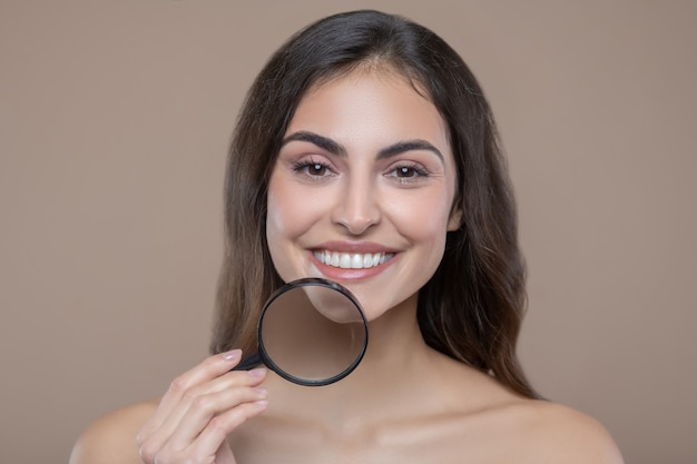 Facial skin care. joyful long haired pretty woman with toothy smile holding magnifying glass near jawline