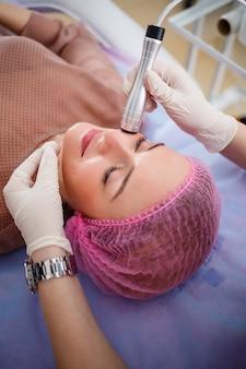 フェイシャルスキンケア。美容院で施術を受ける若い美女。超音波アンチエイジングキャビテーション、若返り、リフティング手順。美容コンセプト