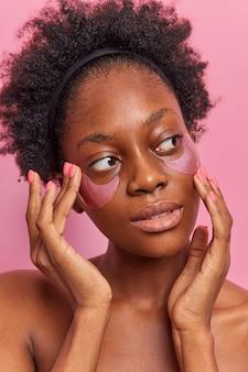 Уход за кожей лица. молодая женщина наносит розовые гидрогелевые патчи под глаза для увлажнения использует современные косметические средства уменьшает отечность смотрится задумчиво вдали стоит без рубашки в помещении