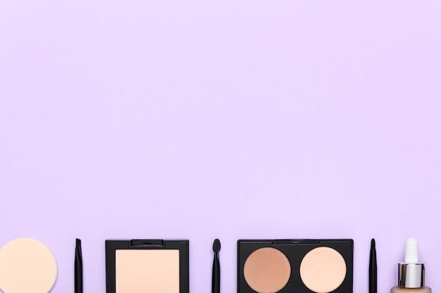 Facial skin correction cosmetics on light purple background. sponge, facial powder, brushes