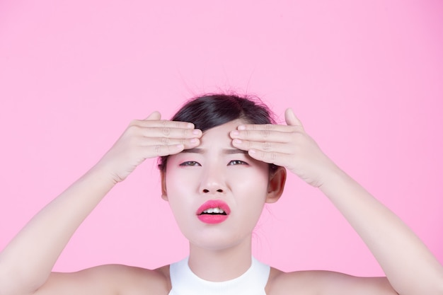 Facial skin problems women - unhappy young women touching her skin on a pink background.