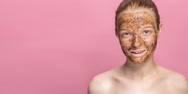 美しい若い女性の顔にフェイシャルスキンスクラブコーヒーグラウンズマスク