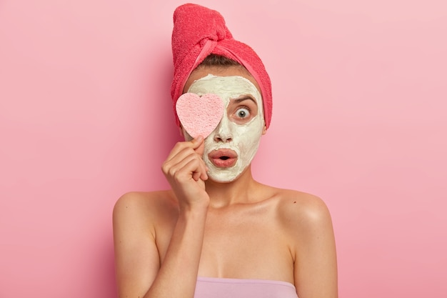 페이셜 트리트먼트 및 스파 개념. 놀란 젊은 여성이 점토 마스크를 바르고, 빠른 효과로 충격을 받고, 화장품 스폰지를 눈에 유지하고, 분홍색 벽에 알몸으로 서서, 피부를 치료합니다.