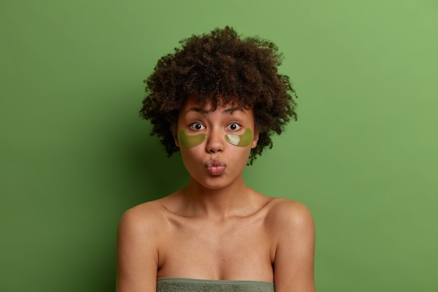 Facial treatment concept. lovely young refreshed woman with afro hairstyle, uses green patches under eyes, rounds lips, stands wrapped in towel, has natural beauty, poses over green wall