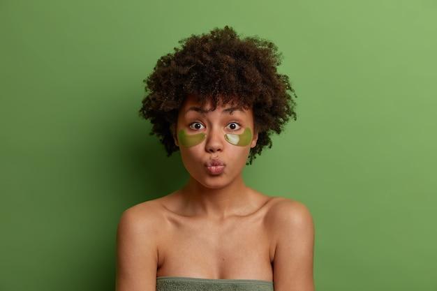 페이셜 트리트먼트 개념. 아프로 헤어 스타일을 가진 사랑스러운 젊은 상쾌한 여자는 눈 아래에 녹색 패치를 사용하고, 입술을 둥글게하고, 수건으로 싸서 서 있으며, 자연의 아름다움을 가지고 있으며, 녹색 벽 위에 포즈를 취합니다.