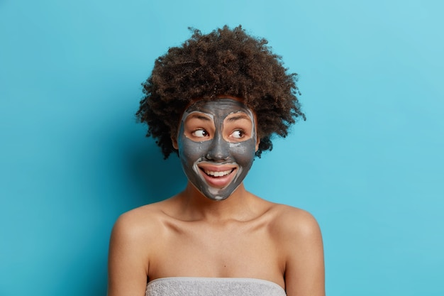 Facial treatment concept. positive curly haired woman applies clay mask on face to rejuvenate skin undergoes beauty procedures after taking shower poses wrapped in towel isolated over blue wall