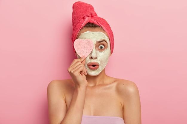 Trattamento viso e concetto spa. la giovane donna stupita applica una maschera all'argilla, scioccata dal risultato rapido ed efficace, mantiene la spugna cosmetica sugli occhi, sta nuda contro il muro rosa, guarisce la pelle