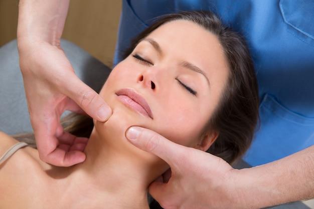 Терапия массажа лица с помощью туина на лице красивой женщины