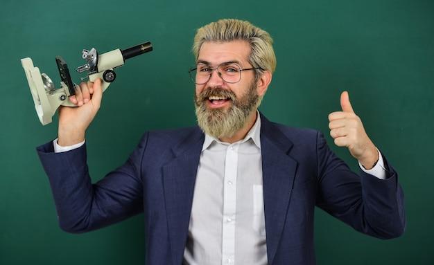 学業の進歩を促進します。魅力的な研究。顕微鏡の先生。男ヒップスター教室黒板背景。生物学的研究。顕微鏡を探している学校の先生。科学研究。