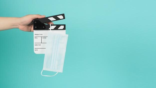 カチンコと手の偽のマスクは、カチンコまたは映画のスレートを保持しています。これは、グリーンミントまたはティファニーブルーの背景で映画制作や映画業界で使用されています。