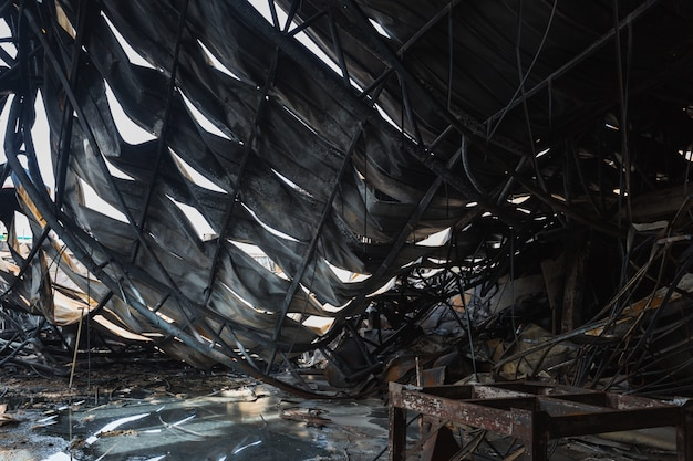 Factory after the fire. burnt out warehouse with charred roof trusses and burnt products