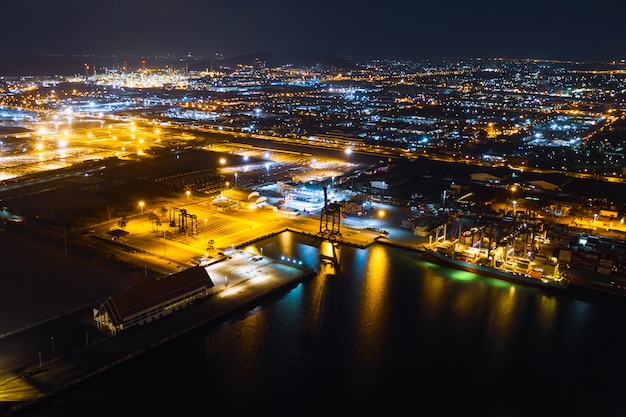Factory area and terminal shipping port cargo container import and export at night