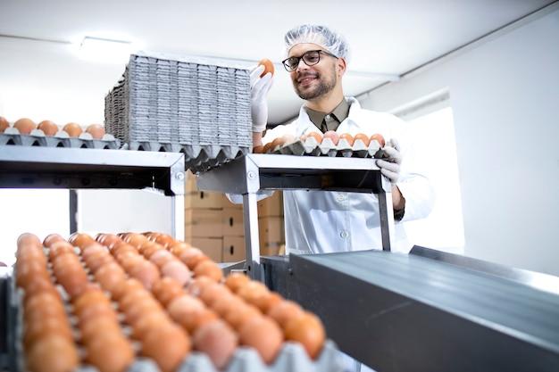 식품 가공 공장에서 계란의 품질을 검사하고 확인하는 공장 직원.