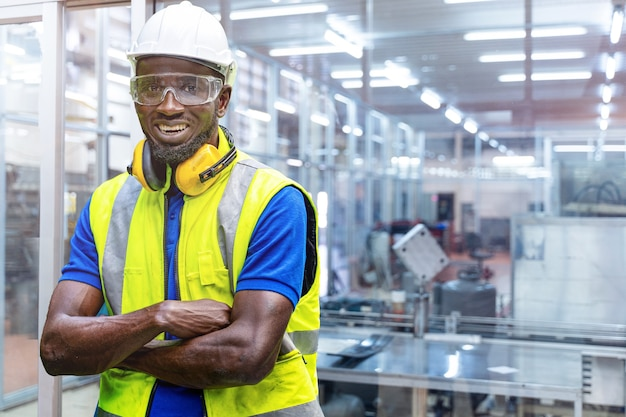 Factory engineer african man standing confidence with green working suite dress and safety helmet
