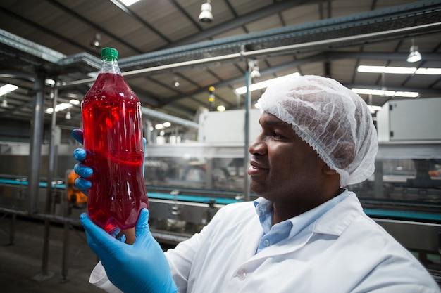ジュースのボトルを保持している工場エンジニア