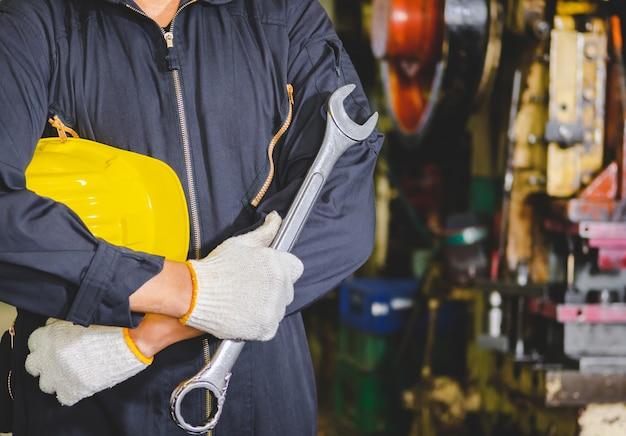 공장 엔지니어는 하드 모자와 렌치를 제복을 입고 준비된 서비스와 산업 내부에서 일하고 있습니다. 공장에서 제복, 헬멧, 장갑, 렌치 산업 노동자.