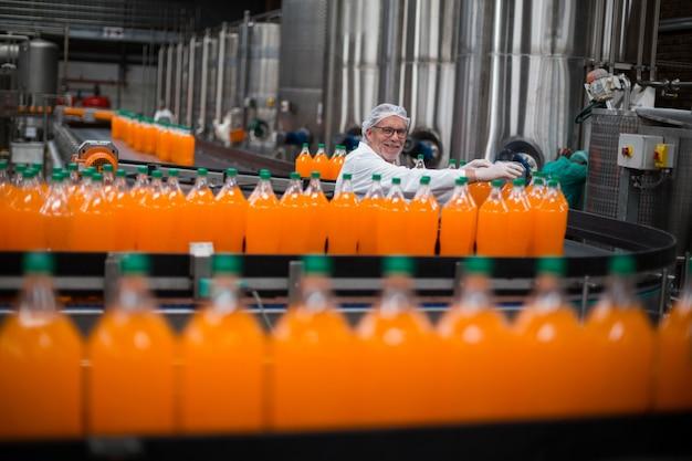 生産ラインで満たされたジュースのボトルを監視する工場エンジニア