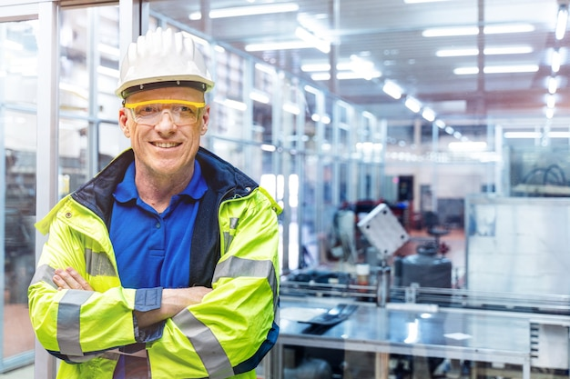 Factory engineer senior man standing confidence with green working suite dress and safety helmet