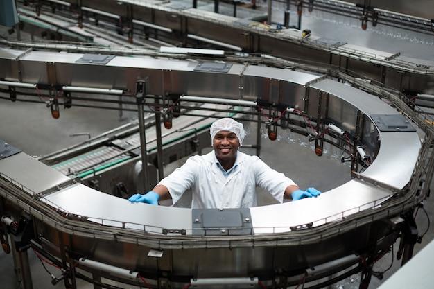 Фабричный инженер стоит рядом с производственной линией