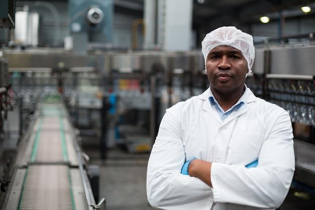 Фабричный инженер, стоя со скрещенными руками на заводе по производству бутылок