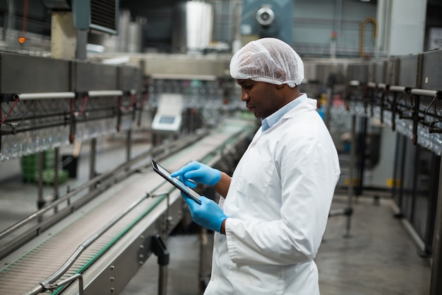 Фабричный инженер с использованием цифрового планшета на заводе