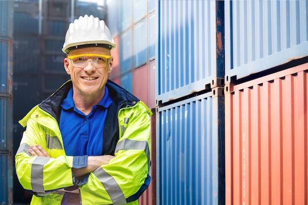 Заводской инженер рабочий человек, стоящий уверенно, в зеленом рабочем костюме и защитном шлеме