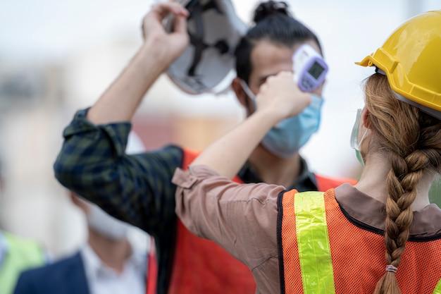 温度をチェックする工場の女性労働者