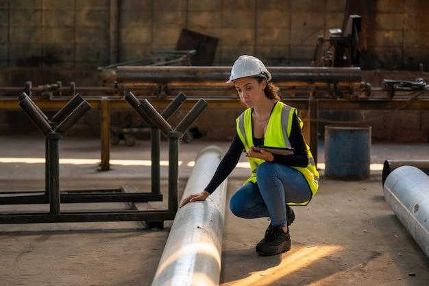 工場で必要なメモを取りながら、クリップボードを手に持って作業している工場の女性労働者。