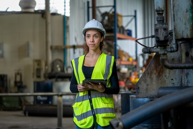 Factory female worker working and checking with clipboard in hands taking necessary notes at plant.