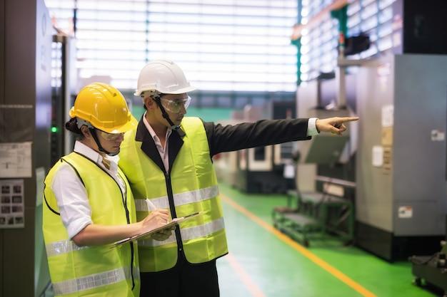공장 검사관이 기계의 감사 결과를 작성하고 관리자가 기계를 가리키며 프리미엄 사진