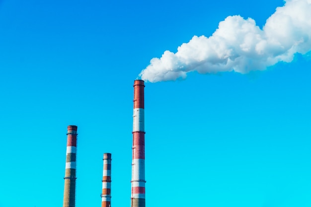 The factory is releasing white smoke of pollution through the big pipe