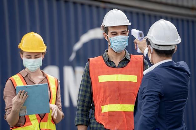 공장 남자 사용 장비는 작업자 온도를 측정합니다.