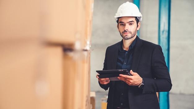 창고 또는 공장에서 태블릿 컴퓨터를 사용하는 공장 관리자. 산업 및 공급망 관리 개념.