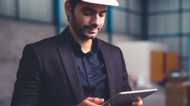 Заводской менеджер с помощью планшетного компьютера на складе или фабрике. концепция управления промышленностью и цепочкой поставок.