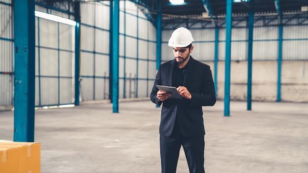 창고 또는 공장에서 태블릿 컴퓨터를 사용하는 공장 관리자